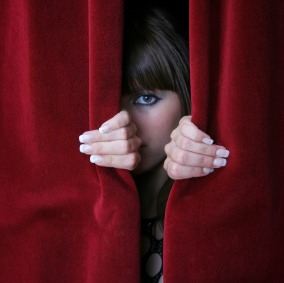 Woman peeping through a red curtain